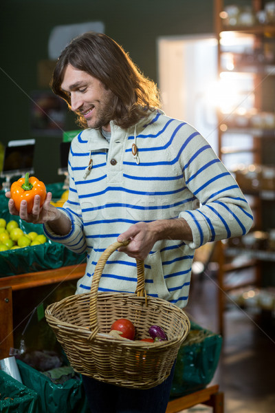 Man with a baskets selecting bell pepper in organic section Stock photo © wavebreak_media