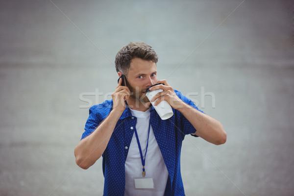 Jóképű férfi iszik kávé beszél mobiltelefon vasút Stock fotó © wavebreak_media