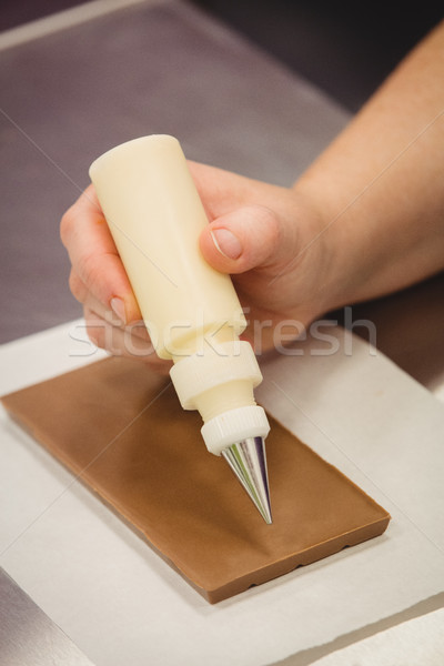 Worker writing with piping bag on chocolate plaque Stock photo © wavebreak_media