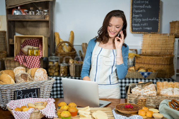 Smiling staff using laptop while talking on mobile phone at bakery counter Stock photo © wavebreak_media