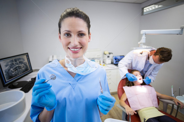Portrait of nurse holding dental tool in clinic Stock photo © wavebreak_media