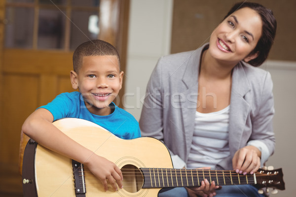 Pretty teacher giving guitar lessons to pupil  Stock photo © wavebreak_media