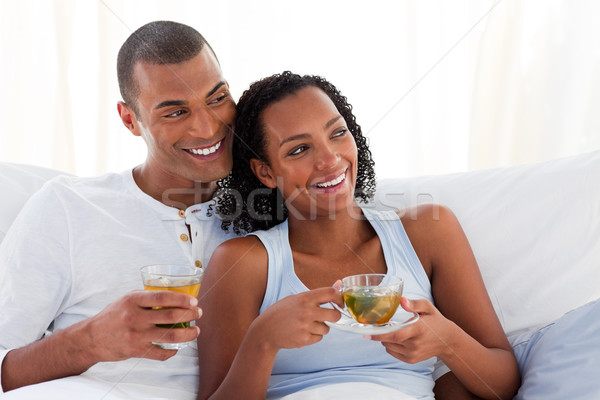 Jolly couple drinking a cup of tea on their bed Stock photo © wavebreak_media