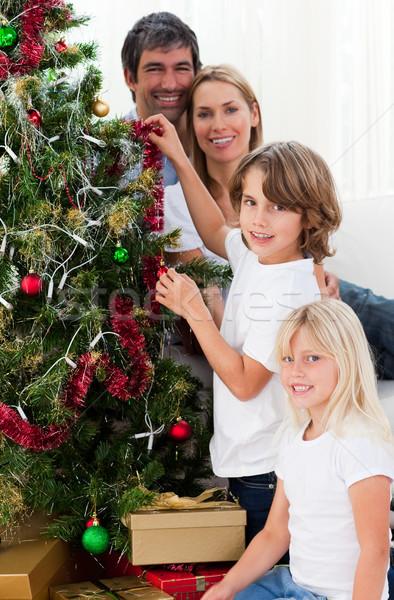 Young family decorating a Christmas tree Stock photo © wavebreak_media