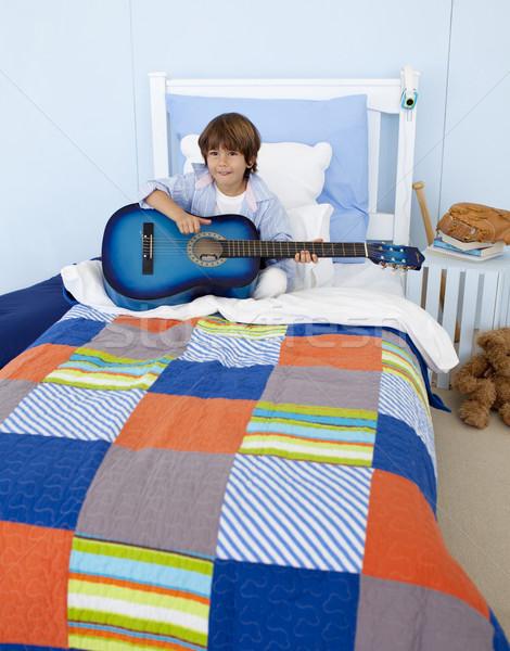 Piccolo ragazzo giocare chitarra camera da letto felice Foto d'archivio © wavebreak_media