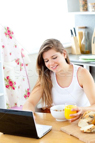 Entusiasta mulher jovem usando laptop café da manhã cozinha casa Foto stock © wavebreak_media
