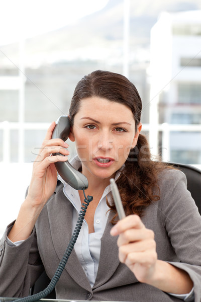 Dissatisfied businesswoman talking on the phone in her office Stock photo © wavebreak_media