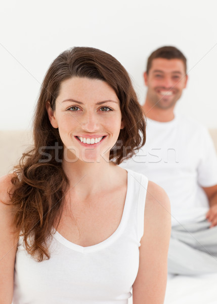 Adorable woman sitting on her bed with her boyfriend in the background Stock photo © wavebreak_media