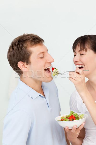 Feliz casal alimentação juntos cozinha mulher Foto stock © wavebreak_media