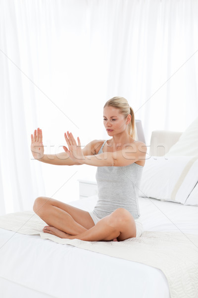 Beautiful woman practicing yoga on her bed Stock photo © wavebreak_media