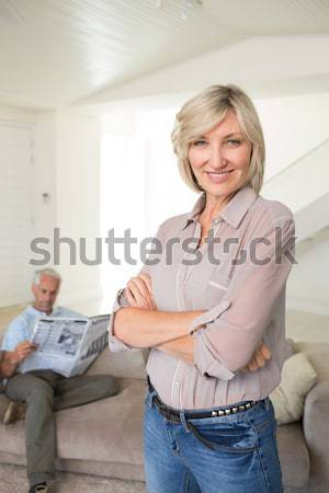 Pretty red-haired woman with a malicious look posing while sitting on a sofa in the living room Stock photo © wavebreak_media