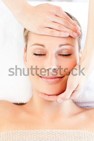 Relaxed blond-haired woman getting a massage on her face in a Spa centre Stock photo © wavebreak_media