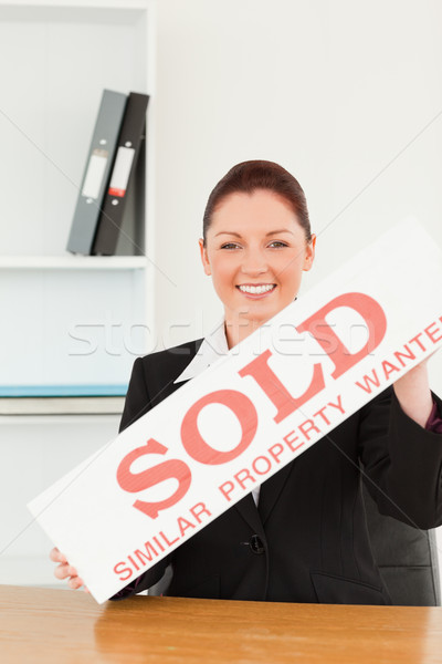 Young real estate agent holding a sold placard in her office Stock photo © wavebreak_media