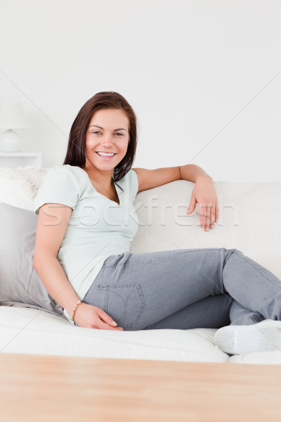 Stock photo: Smiling woman sitting on a couch looking at the camera
