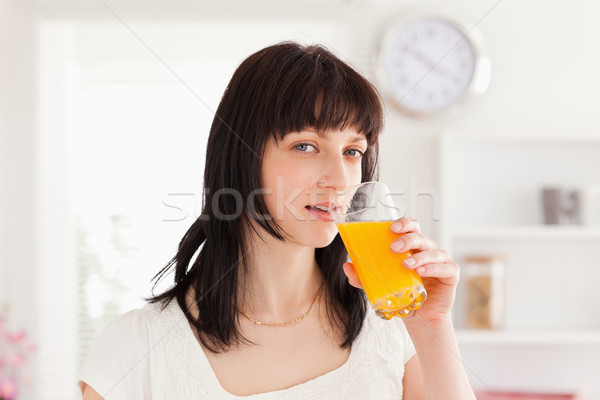 Pretty brunette drinking a glass of orange juice while standing in the kitchen Stock photo © wavebreak_media