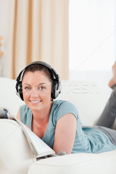 Beautiful woman with headphones reading a magazine while lying on a sofa in the living room Stock photo © wavebreak_media