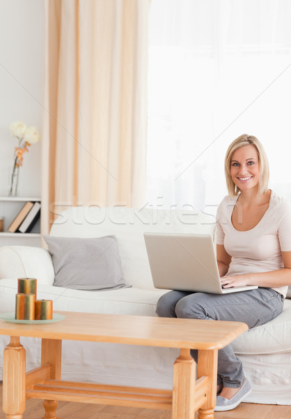 Portrait of a beautiful woman with a laptop in her living room Stock photo © wavebreak_media