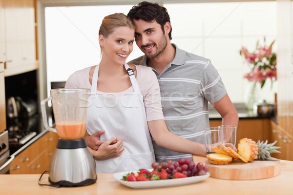 Couple making fresh fruits juice in their kitchen Stock photo © wavebreak_media