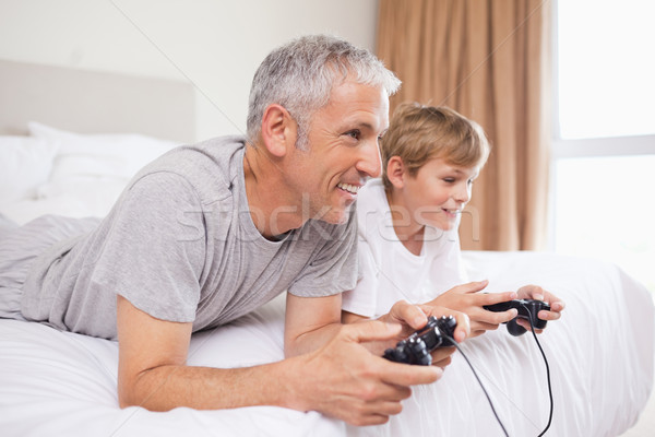 улыбаясь отцом сына играет Видеоигры спальня семьи Сток-фото © wavebreak_media