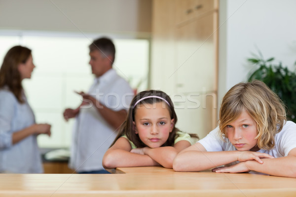 Stock photo: Sad looking siblings with their fighting parents behind them