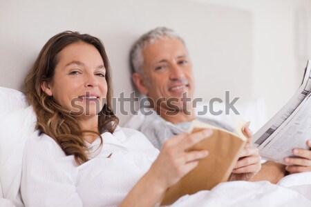 Stockfoto: Gelukkig · glimlachende · vrouw · bed · echtgenoot · lezing · achter