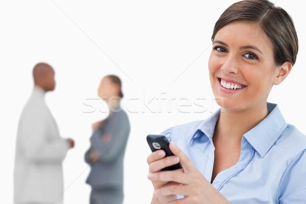 Mosolyog elarusítónő mobiltelefon munkatársak mögött fehér Stock fotó © wavebreak_media