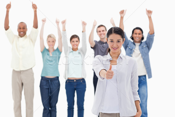Close-up of a girl with people raising their arms and with their thumbs up in background Stock photo © wavebreak_media
