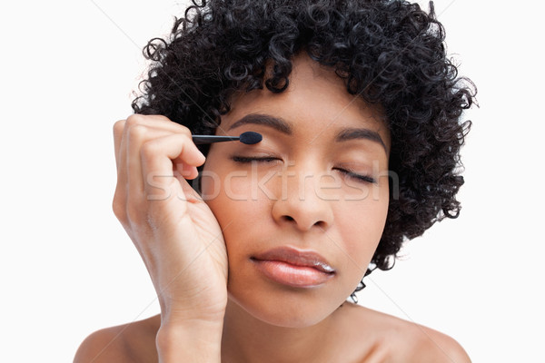 Beautiful female applying eye-shadow and closing her eyes Stock photo © wavebreak_media