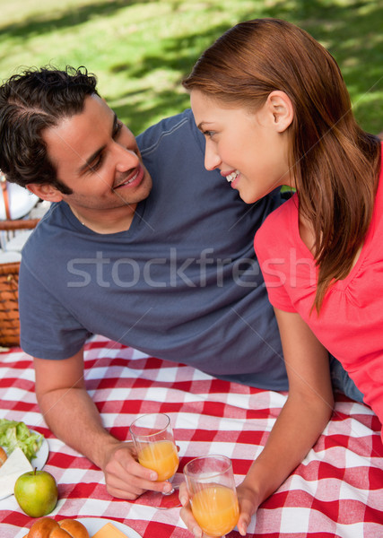 Close-up of two smiling friends looking into each others eyes while they hold glasses as they lie on Stock photo © wavebreak_media