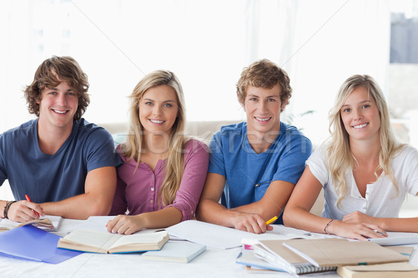 A smiling group of students doing work together as they look at the camera  Stock photo © wavebreak_media