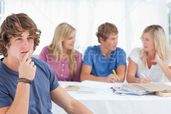 A close up shot of a man sitting in front of his friends as he looks at the camera while he thinks Stock photo © wavebreak_media