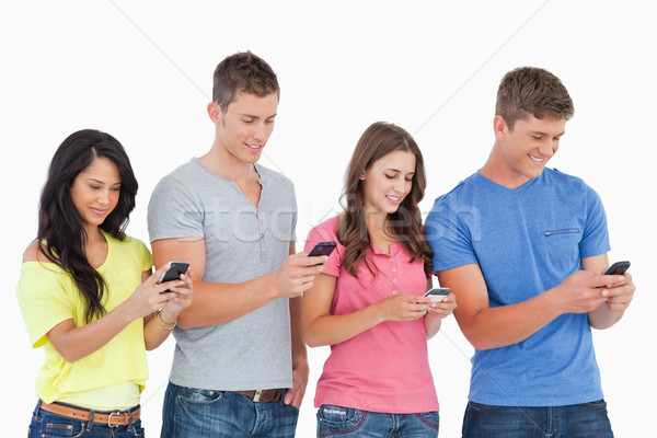 A group of four friends standing slightly to the side as they all send texts on their phones  Stock photo © wavebreak_media