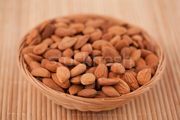 Bowl full of roasted almonds on a wooden placemat Stock photo © wavebreak_media
