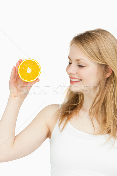 Joyful woman holding an orange against white background Stock photo © wavebreak_media