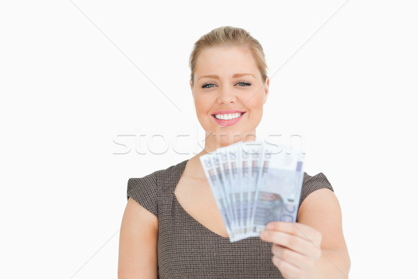 Woman smiling showing euros banknotes against a white background Stock photo © wavebreak_media