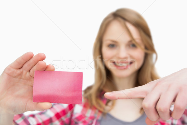 Woman holding a loyalty card while showing it with a finger against a white background Stock photo © wavebreak_media