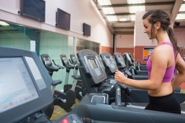 Woman running and training on a treadmill in a gym wearing black shorts and purple top  Stock photo © wavebreak_media
