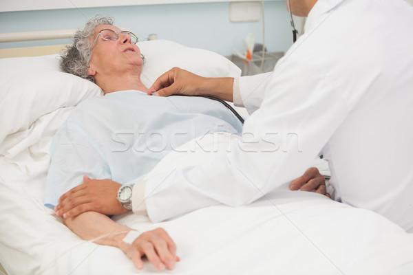 Doctor listening to heartbeat of elderly female patient in hospital bed Stock photo © wavebreak_media