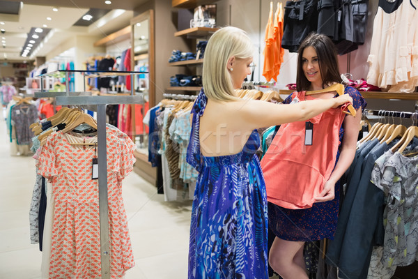 Woman is showing orange shirt to friend in shopping mall Stock photo © wavebreak_media