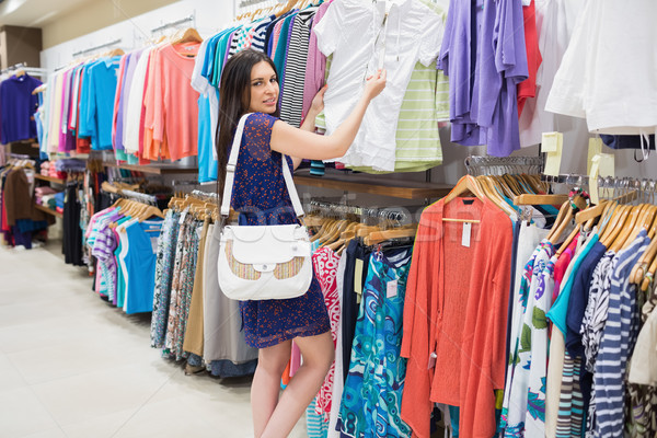 Woman looking at price tag while holding clothes at the shopping mall Stock photo © wavebreak_media