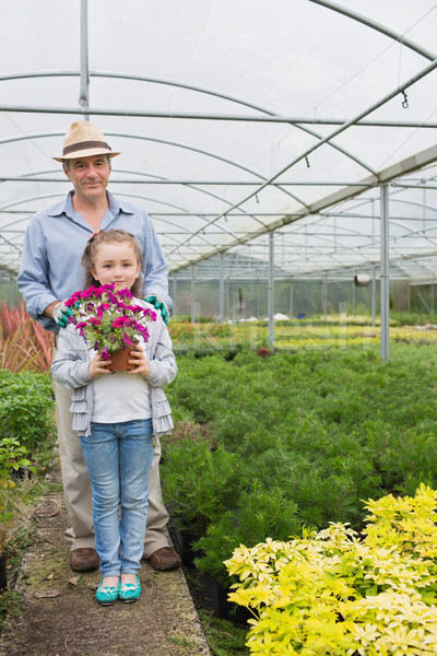Little girl holdiong flower pot standing with her granddad in the greenhouse Stock photo © wavebreak_media