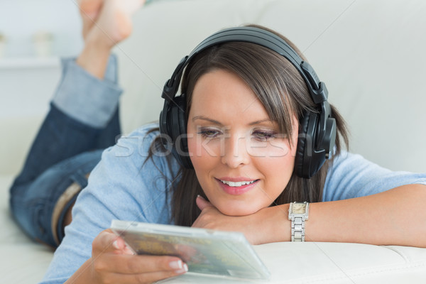 Happy woman listening music looking at cd on sofa in the living room Stock photo © wavebreak_media