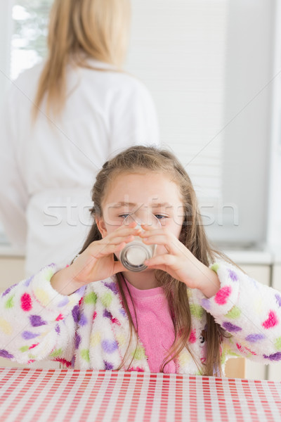 Child sitting drinking milk at the kitchen in the morning Stock photo © wavebreak_media