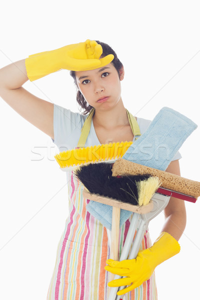 Tired woman in apron and rubber gloves holding cleaning tools Stock photo © wavebreak_media