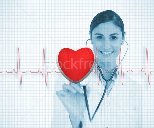 Stock photo: Doctor holding stethoscope up to red ECG line with heart graphic