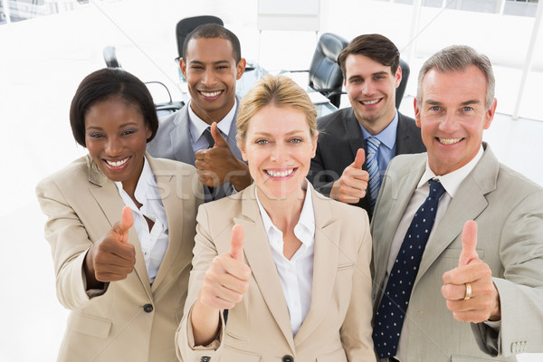 Diverse close business team smiling up at camera giving thumbs u Stock photo © wavebreak_media