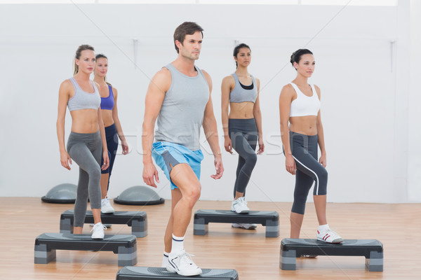 Instructor with fitness class performing step aerobics exercise Stock photo © wavebreak_media