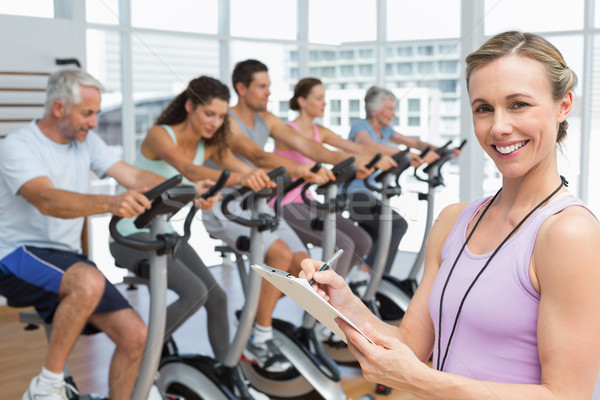 Trainer with people working out at spinning class Stock photo © wavebreak_media