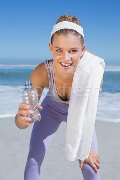 Deportivo sonriendo pie toalla de playa botella Foto stock © wavebreak_media