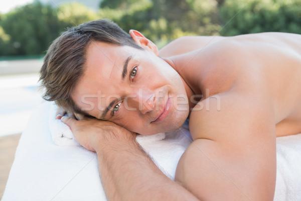 Peaceful man lying on massage table poolside Stock photo © wavebreak_media